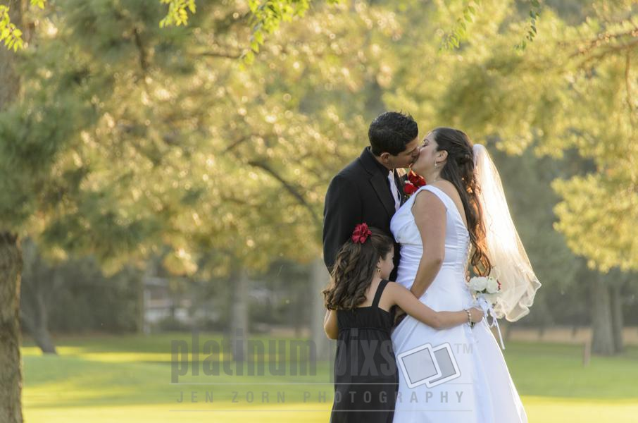 Bride and Groom Kissing with Daughter